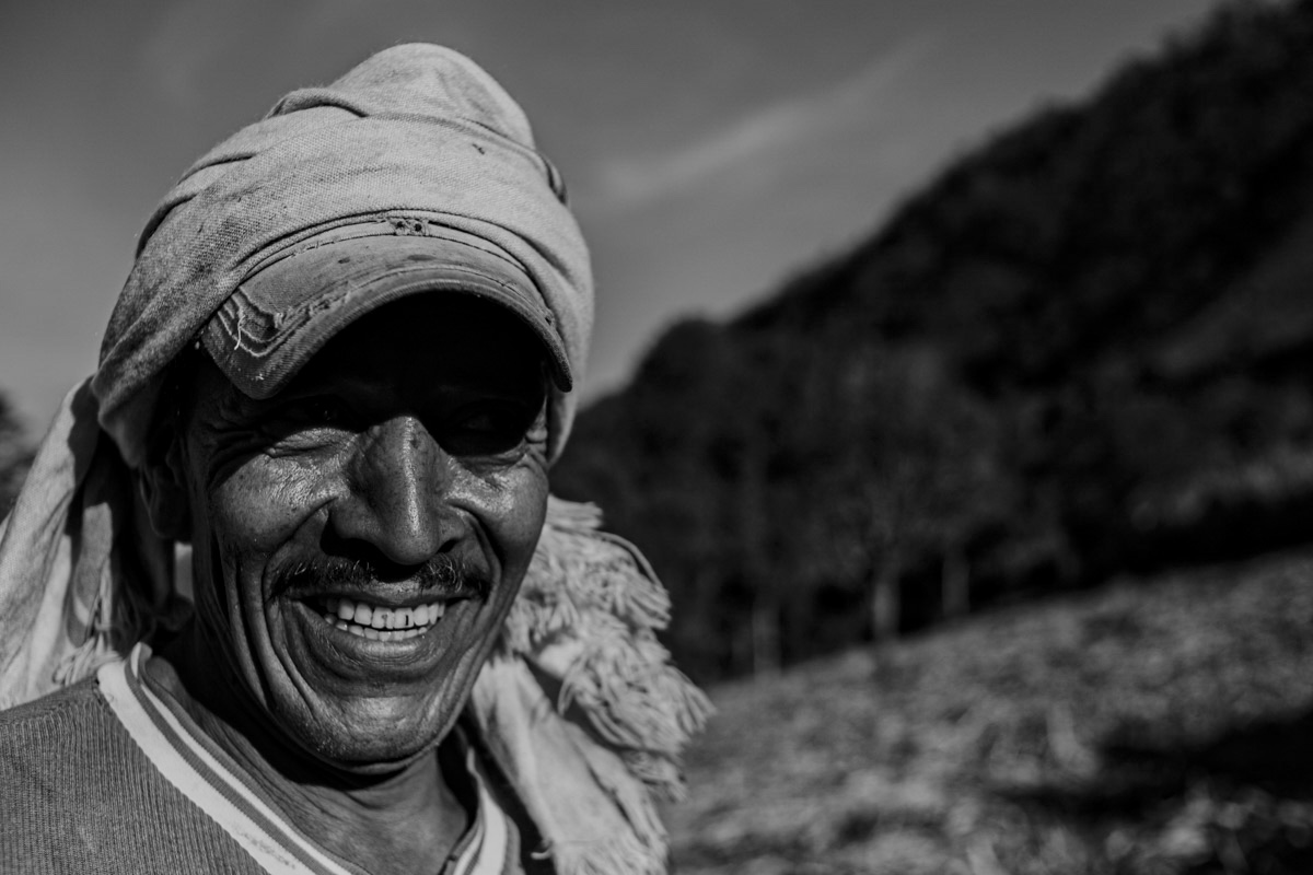 This portrait features a mustached man, his grin revealing brown vertical marks on his two front teeth. His sweat stained cap is wrapped in a towel, protecting him from the beating sun in this open valley. Behind him, beyond where the sugarcane grows, a steep hill of lush greenery offers relief from the sun.